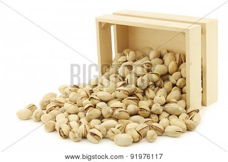 Pistachio nuts in a wooden box on a white background