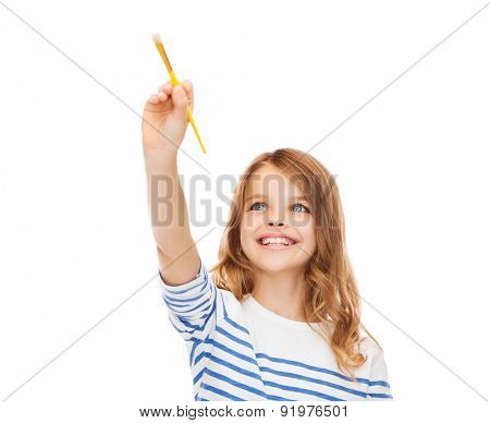 education, school and imaginary screen concept - cute little girl drawing with brush in the air or imaginary screen