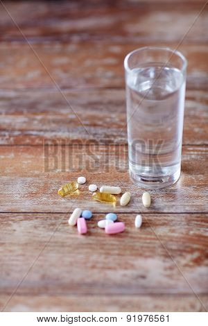 medicine, nutritional supplements and food additives concept - - close up of vitamin pills with cod liver oil capsules and water glass on table