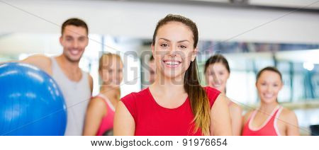 fitness, sport, training, gym and lifestyle concept - smiling woman standing in front of the group of people in gym