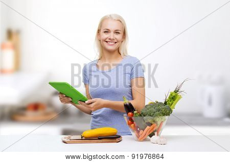 healthy eating, cooking, vegetarian food, technology and people concept - smiling young woman with tablet pc computer and bowl of vegetables over home kitchen background