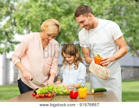 vegetarian food, culinary, happiness and people concept - happy family cooking vegetable salad for dinner over house and summer garden background