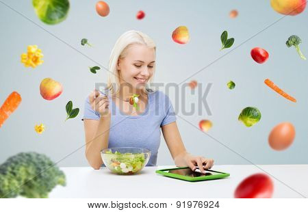 healthy eating, dieting and people concept - smiling young woman with tablet pc computer eating vegetable salad over gray background with falling vegetables