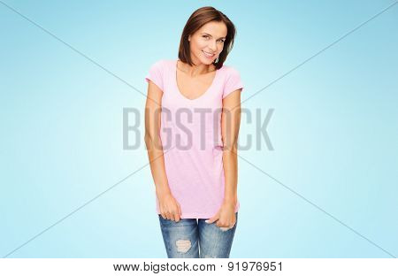 people, advertisement and clothing concept - happy woman in blank pink t-shirt over blue background