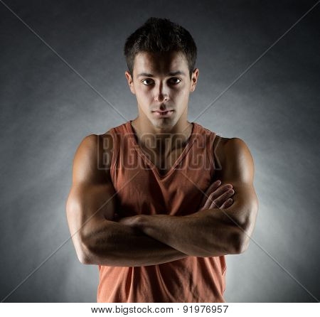 sport, bodybuilding, strength and people concept - young man standing over gray background