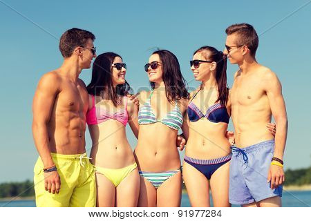 friendship, sea, summer vacation, holidays and people concept - group of smiling friends wearing swimwear and sunglasses talking on beach