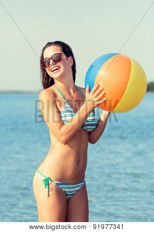 sea, summer vacation, holidays, sport and people concept - smiling teenage girl sunglasses with inflatable ball on beach