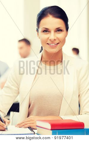 business concept - attractive businesswoman taking notes in office