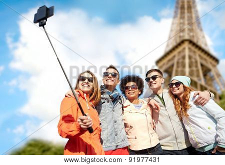 tourism, travel, people, leisure and technology concept - group of smiling teenage friends taking selfie with smartphone and monopod over paris eiffel tower background