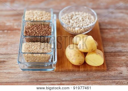 diet, cooking, culinary and carbohydrate food concept - close up of grain and beans in glass bowls with potatoes on table