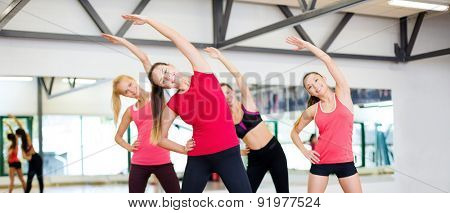fitness, sport, training, gym and lifestyle concept - group of smiling women stretching in the gym