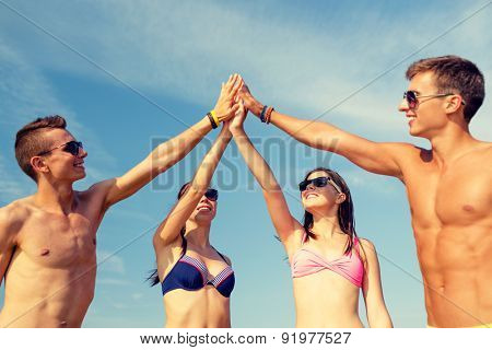 friendship, sea, holidays, gesture and people concept - group of smiling friends wearing swimwear and sunglasses making high five on beach