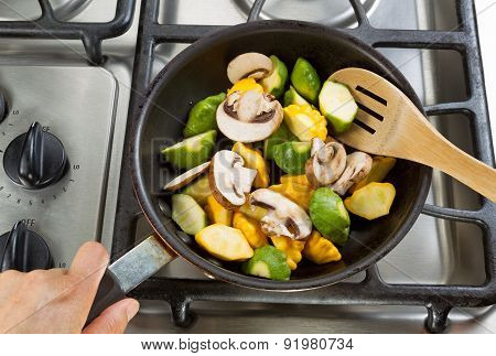 Stirring Vegetables In Frying Pan With Wooden Spoon