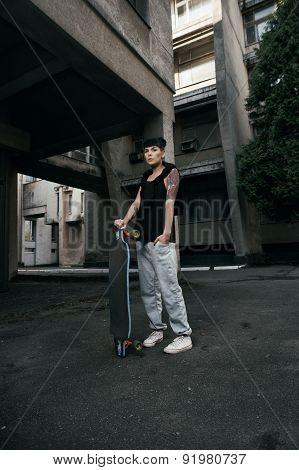 tattooed lady stands with longboard in backyard
