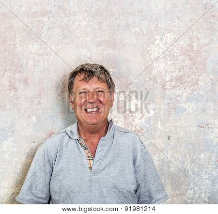 Portrait Of Senior Man In Front Of Grungy Old Wall