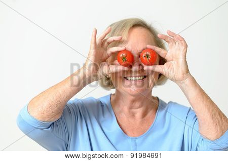 Playful Senior Lady Holding Tomatoes To Her Eyes