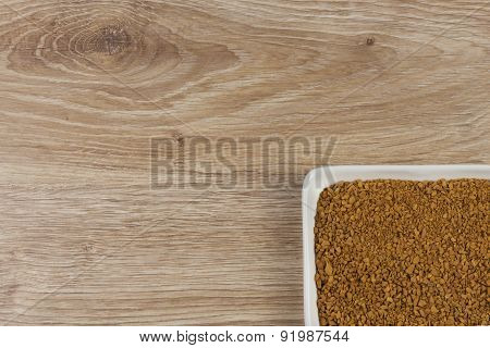 instant soluble coffee and coffee beans in a porcelain bowl on wooden background
