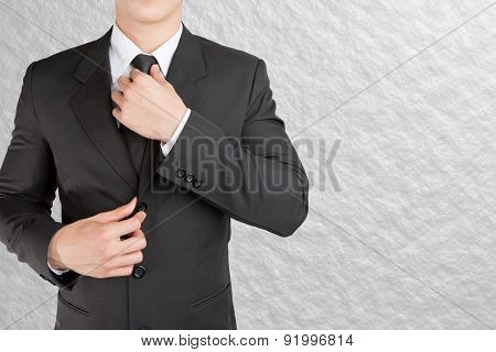 Well dressed businessman looklike smart adjusting  his neck tie on color background : fill text