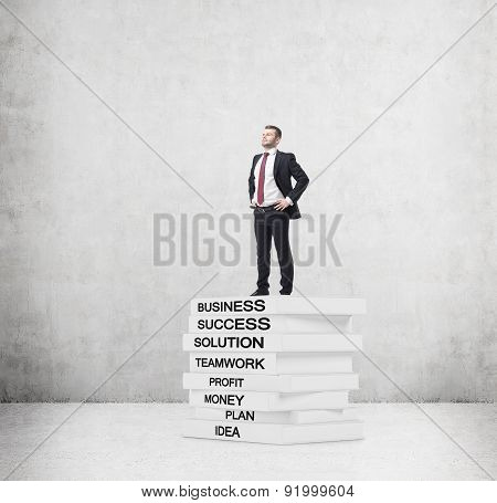 A Student In A Formal Suit Is Standing On The Top Of The Book Pedestal