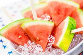 picture of watermelon slices  - Watermelon slice popsicles on serving plate with ice - JPG