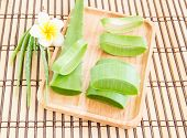 picture of bamboo leaves  - Fresh aloe vera leaf in wooden plate on bamboo mat - JPG