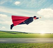 stock photo of cloak  - serious businessman dressed as a superhero in red mask and cloak flying at outdoor over beautiful landscape background - JPG