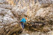 foto of trailblazer  - Woman is climbing on metal ladder in via ferrata - JPG