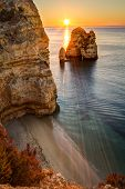 image of lagos  - Sunrise with rays of light shining over rock formation and small beach on Lagos coastline - JPG