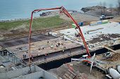 picture of concrete pouring  - Building a new subdivision on the shore of lake Ontario pouring concrete in the foundation - JPG