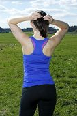 image of ponytail  - backside of young woman on a green field fixing her ponytail - JPG