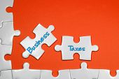 pic of income tax  - Business Taxes word on white puzzle  - JPG