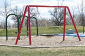 pic of swingset  - Pair of green and red chain link swing sets at an outdoor park - JPG