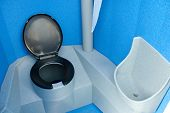 foto of porta-potties  - clean new and unused blue and black portable toilet - JPG