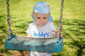 pic of swing  - Little boy grabbing the chain of the swing and trying to get on it to swing - JPG