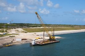 stock photo of dredge  - Dredging shore line and adding stone barrier wall using a barge to transport excavator - JPG