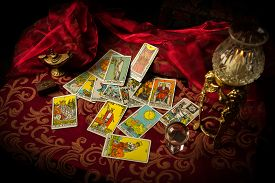 picture of occult  - A pile of tarot cards lie scattered and spread across a table top surrounded by multiple occult items - JPG