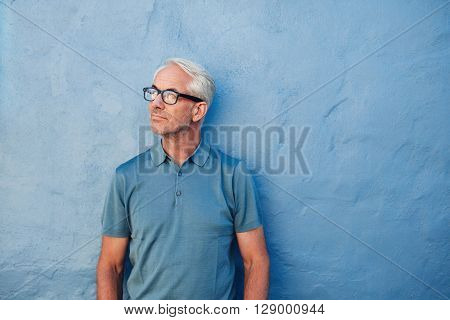 Pensive Mature Man Standing Against A Blue Wall
