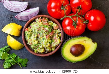 Guacamole and ingredients - avocado, tomatoes, onion, cilantro dark background. Top view