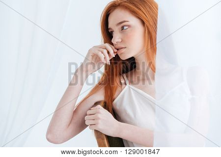 Thoughtful redhead woman sitting on the chair and looking away isolated on a white background