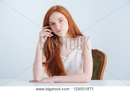 Charming redhead woman sitting at the table and looking at camera isolated on a white background