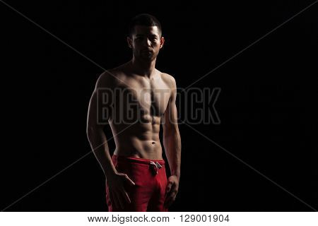 Silhouette of a muscular man standing over dark background