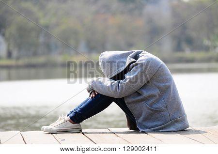 Close up sad woman sitting near river