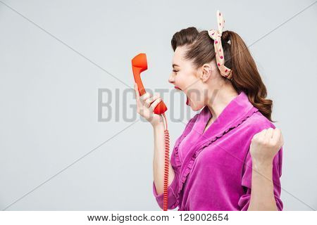 Desperate young housewife holding red telephone receiver and shouting