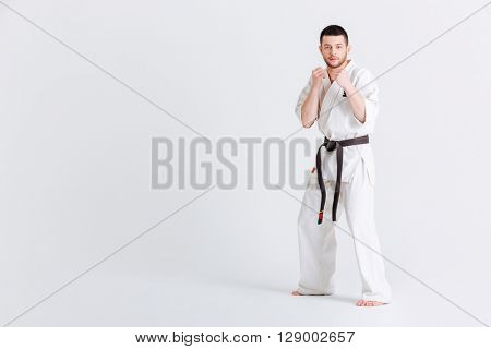Man in kimono standing in fight stance isolated on a white background