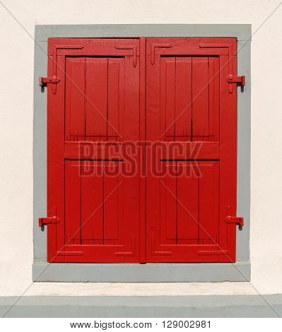 Window with red closed shutter in a gray frame