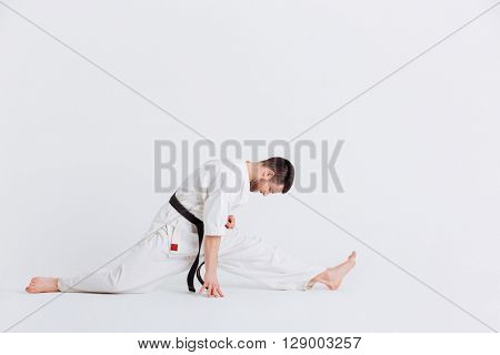 Man in kimono doing stretching exercises isolated on a white background
