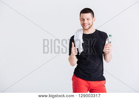 Happy sports man holding bottle with water and showing thumb up isolated on a white bakground