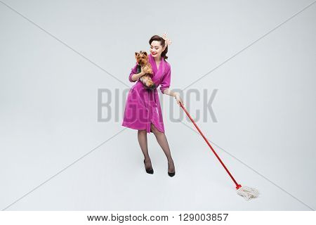 Full length of happy attractive young housewife with mop holding a dog