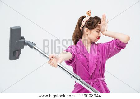 Unhappy tired young woman giving vacuum cleaner to you