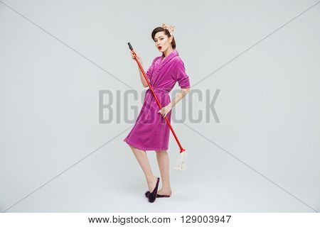 Happy beautiful young housewife standing and posing with mop